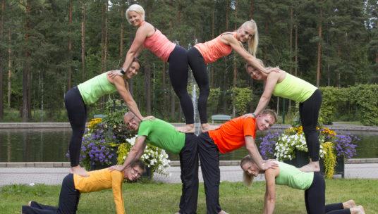Liikunnanohjaajat ovat ryhmittyneet pyramidimuodostelmaan