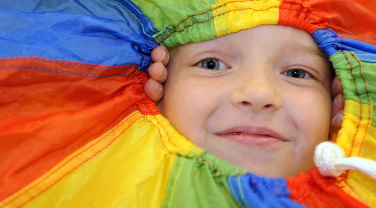 Lapsi kurkistaa värikkään kankaan keskeltä hymyillen