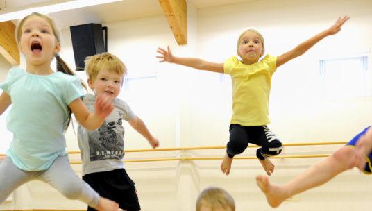 Lapsijoukko hyppää ilmaan iloisena liikuntasalissa