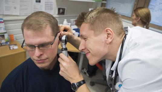 Lääkäri tutkii vastaanotolla potilaan korvaa