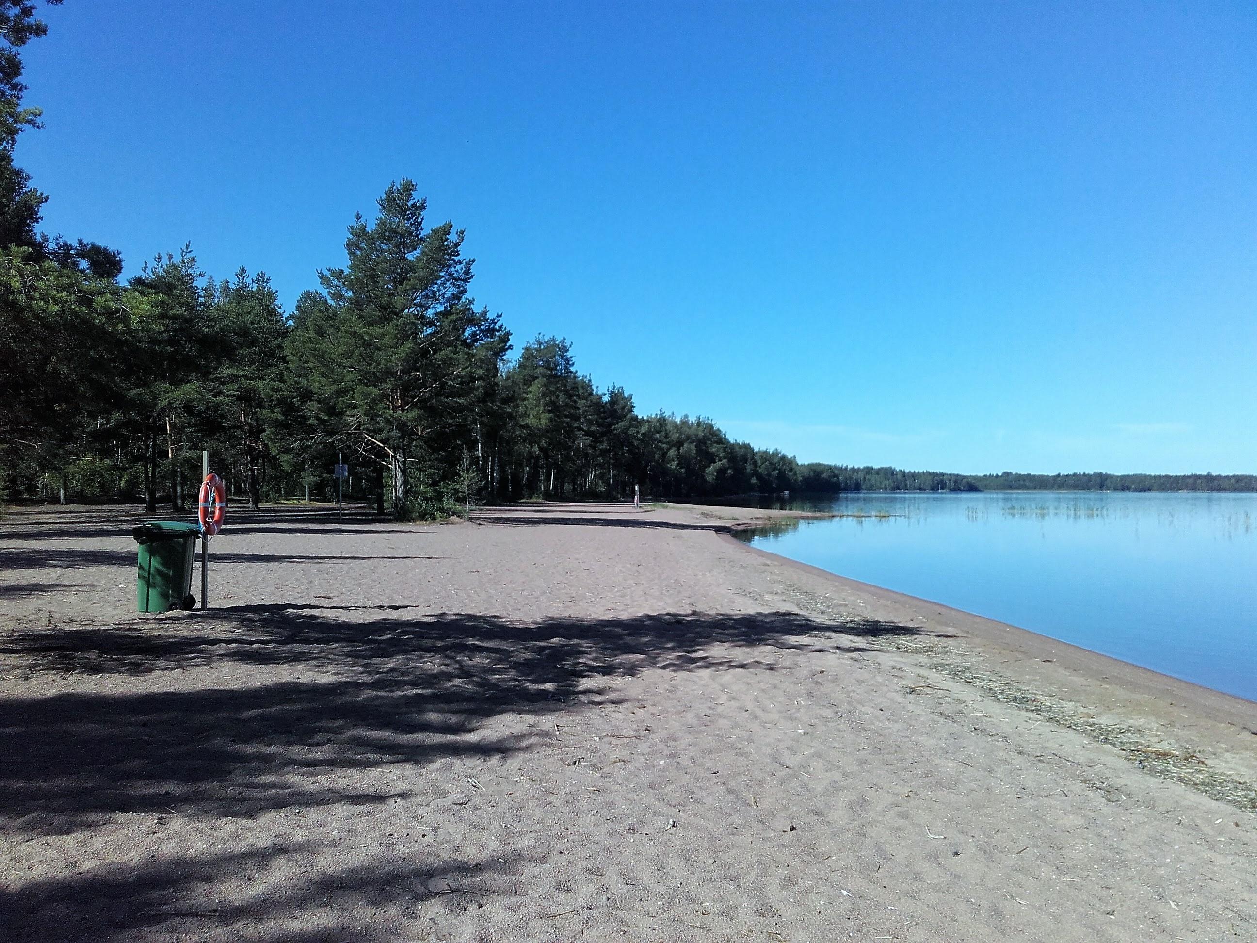 Särkkien uimaranta. Tasainen hiekkaranta. Hiekkarannalla vihreä roskakori ja telineessä pelastusrengas