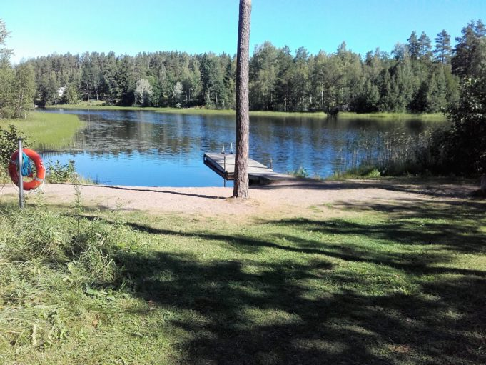 Kuvassa Lautaron uimaranta. Rannalla kasvaa iso puu. Vedessä uimalaituri.
