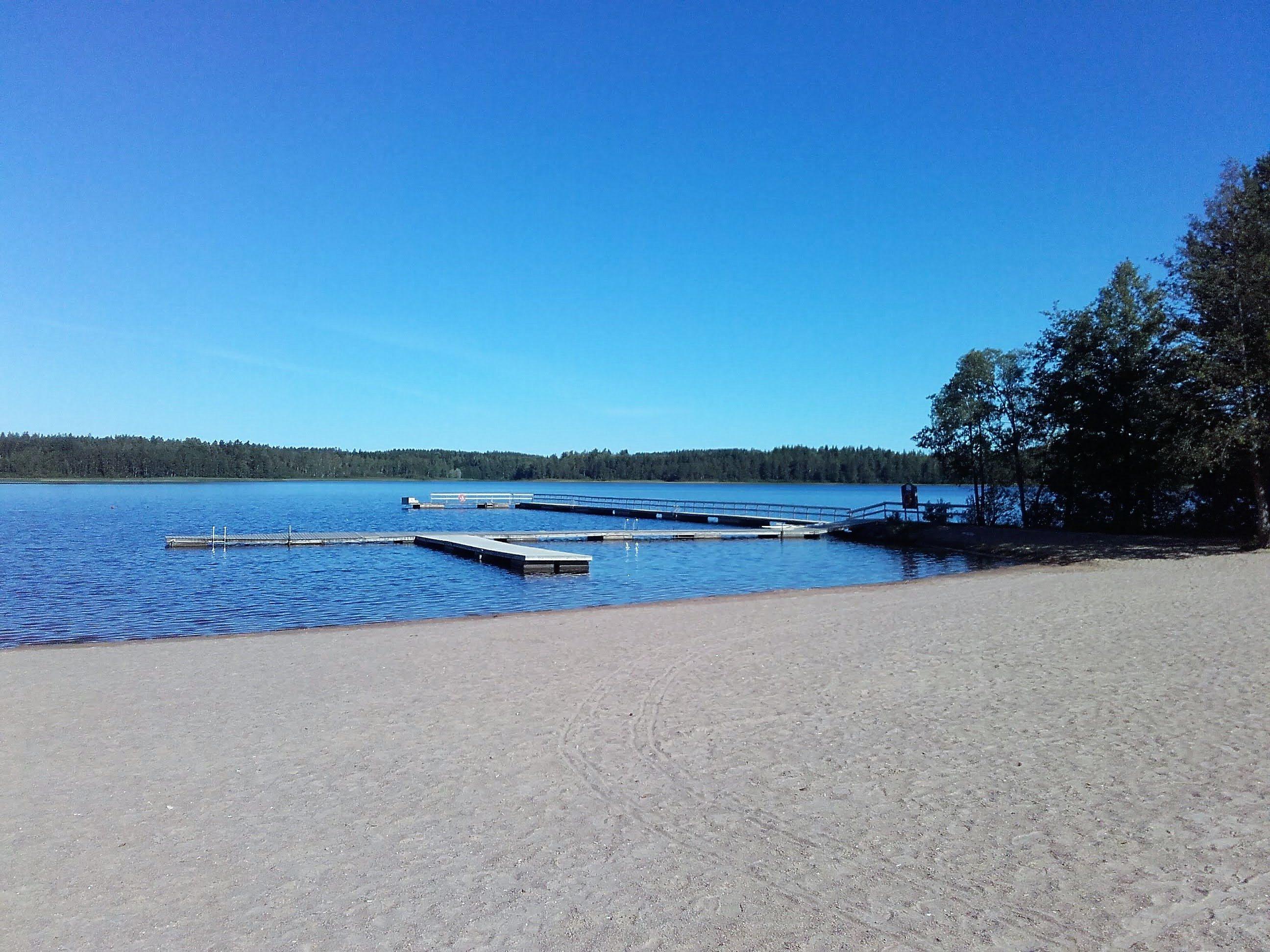 Käyrälammen uimaranta. Kesäinen hiekkaranta. Järvessä pitkä laituri.