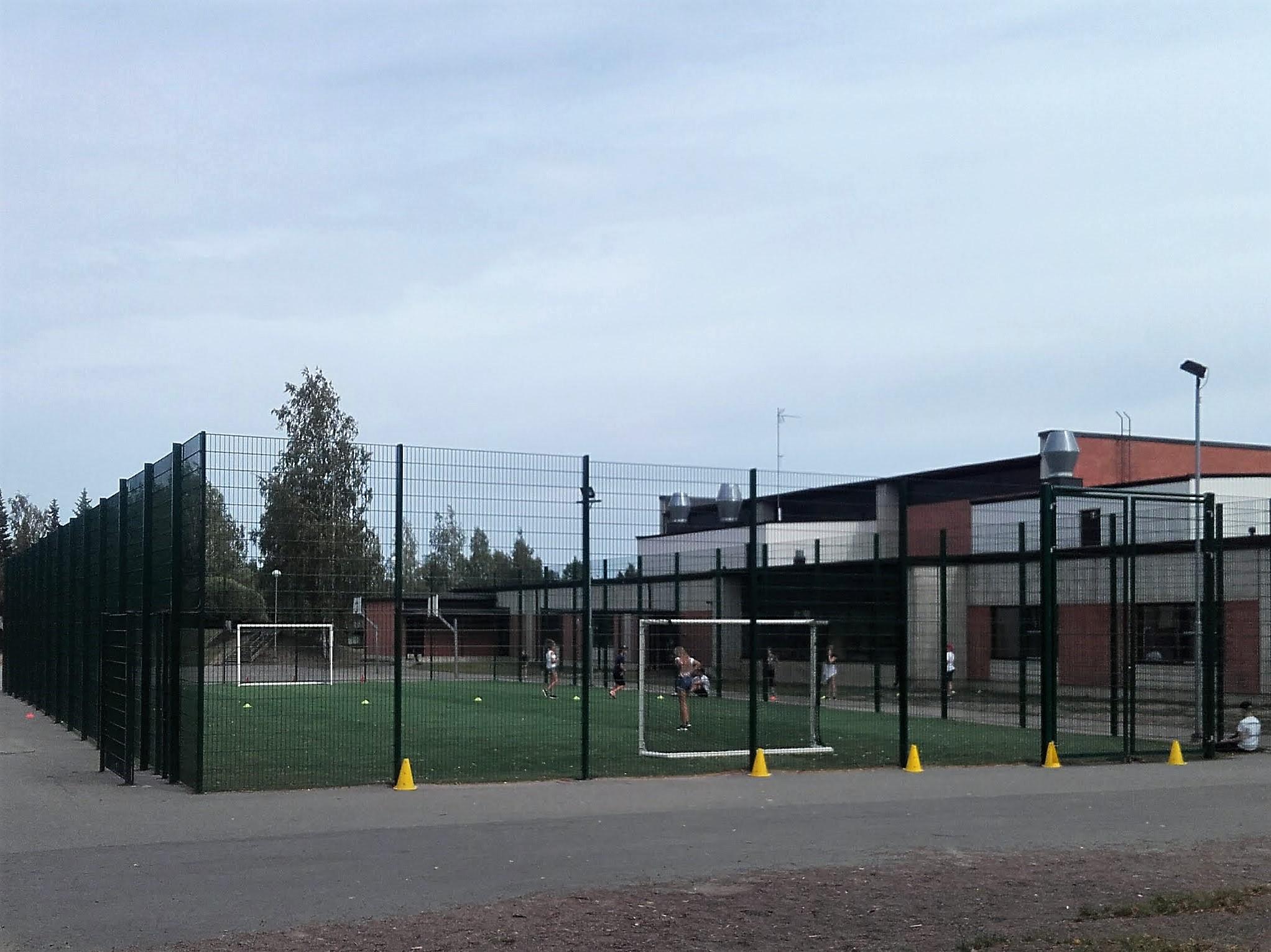 Koulurakennuksen edessä korkealla metalliverkkoaidalla rajattu tekonurmikenttä. Kentän molemmissa päissä maalit.
