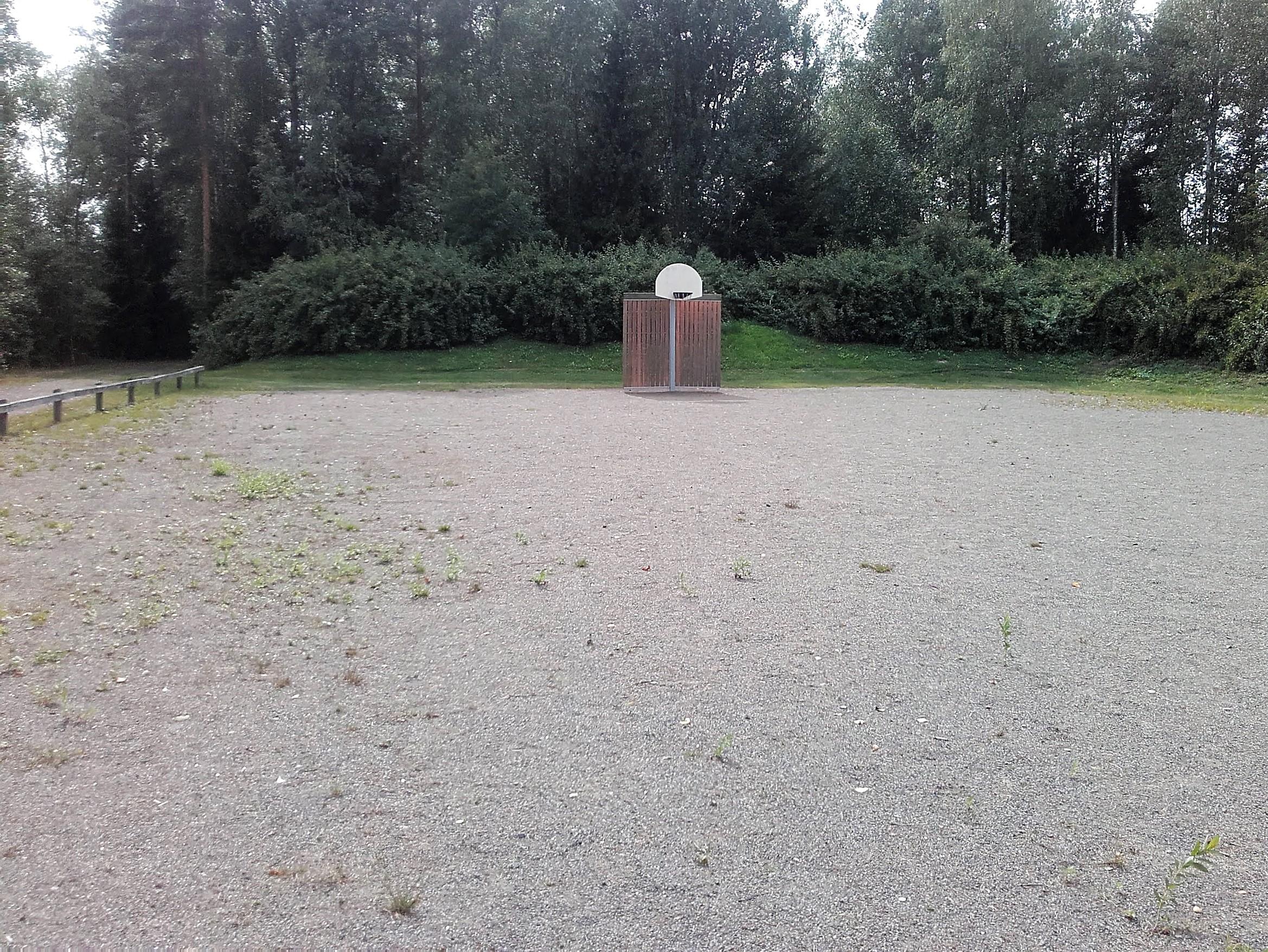 Hiekkakenttä jonka takana kasvaa mestää. Hiekkakentällä koripalloteline sekä pieni maaliseinä.