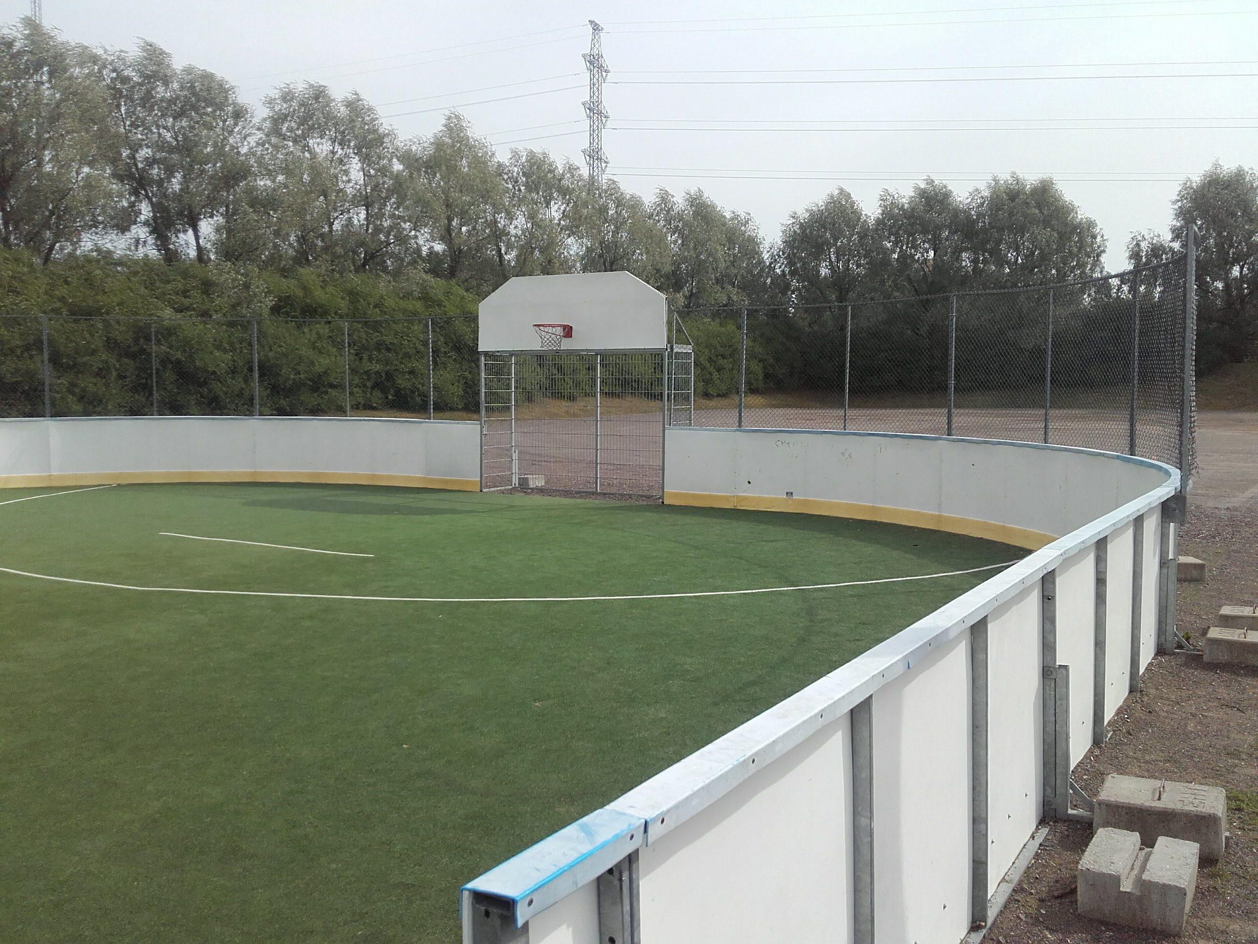 Tekonurmialue jossa jääkiekkokaukalon laidat. Kaukalon toisessa päässä koripalloteline ja jalkapallomaali.