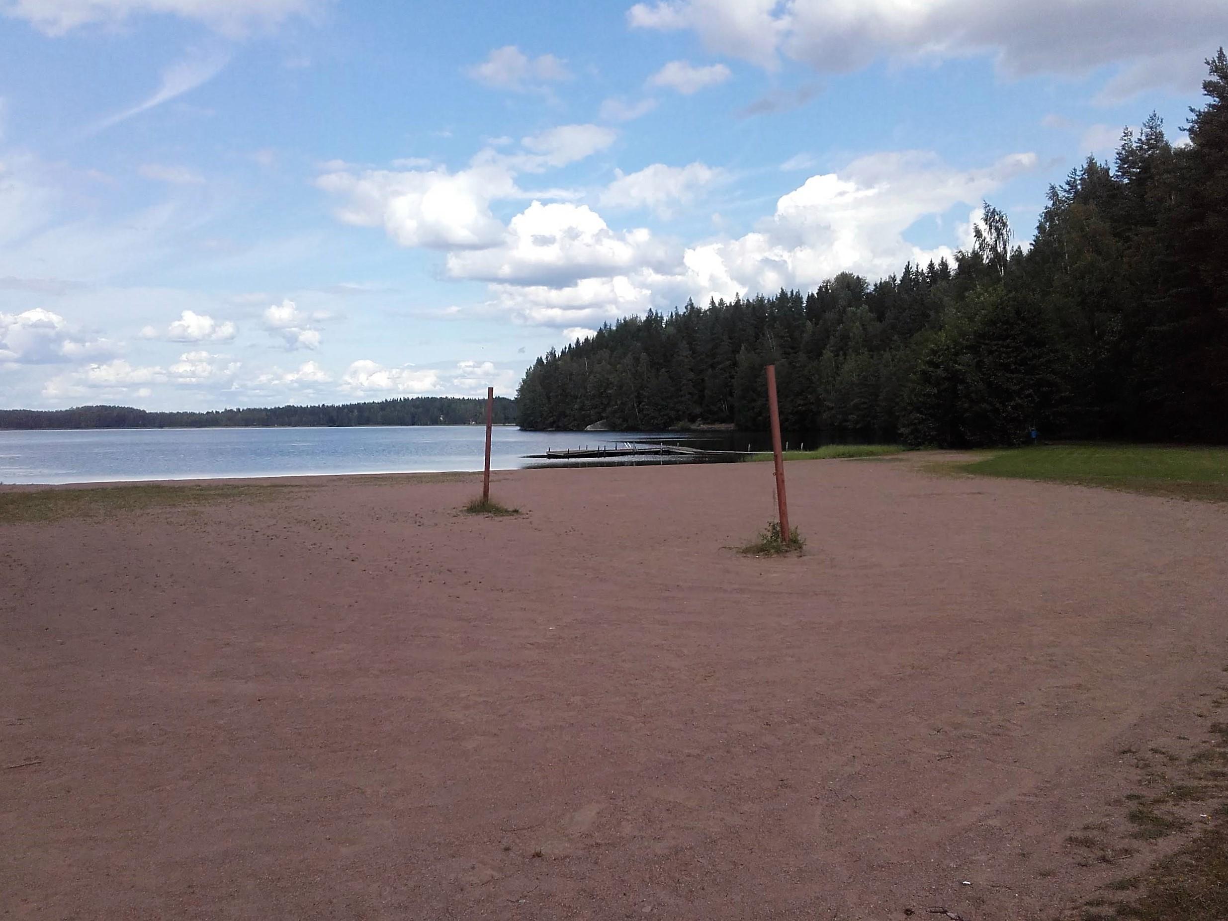 Sompasen uimaranta. Tasainen hiekkaranta. Rannalla tolpat lentopalloverkolle. Taustalla metsää.
