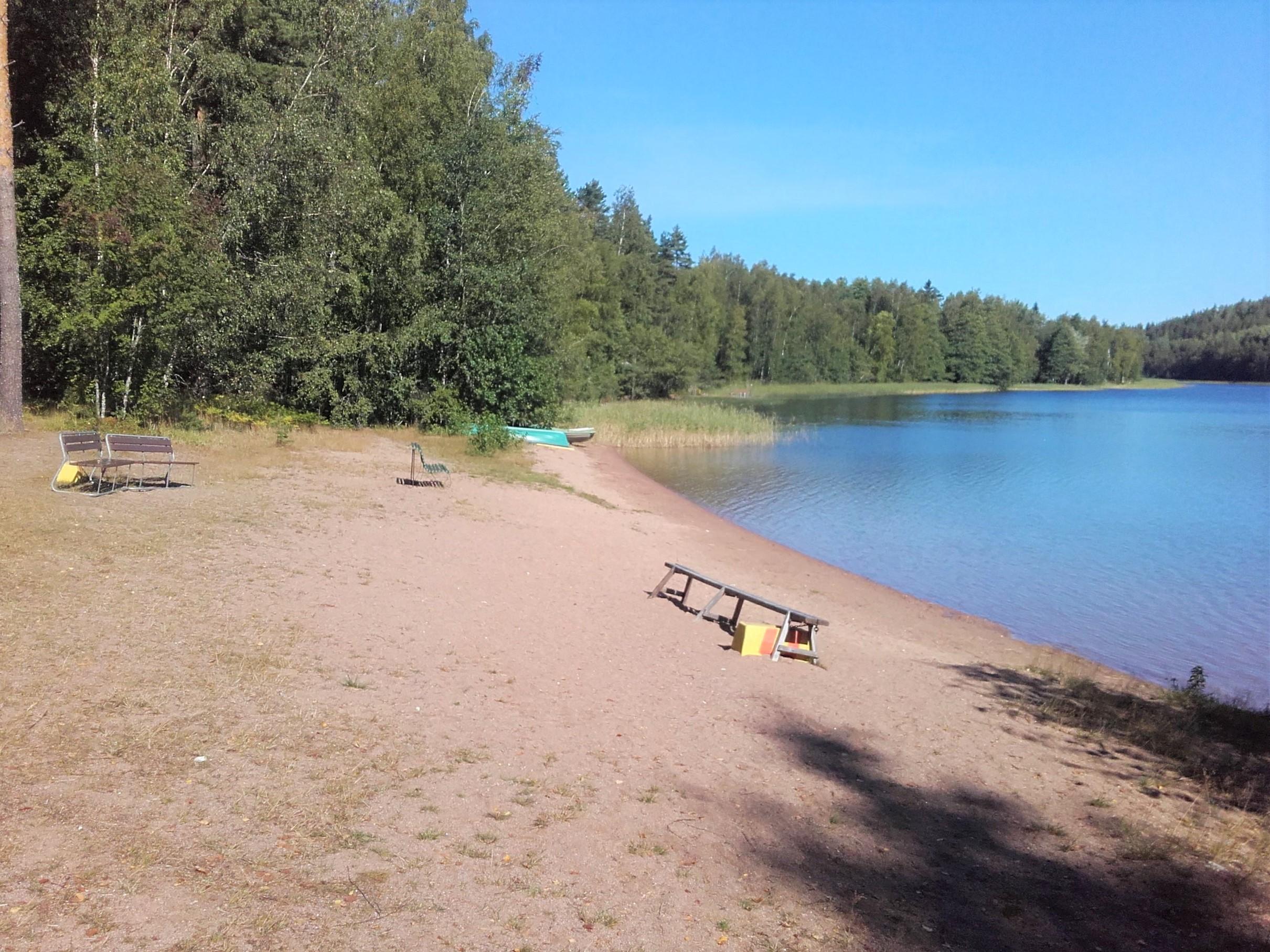 Aurinkoinen hiekkaranta. Rannalla penkkejä istumista varten. Rannan ja lammen ympärillä kasvaa metsää.
