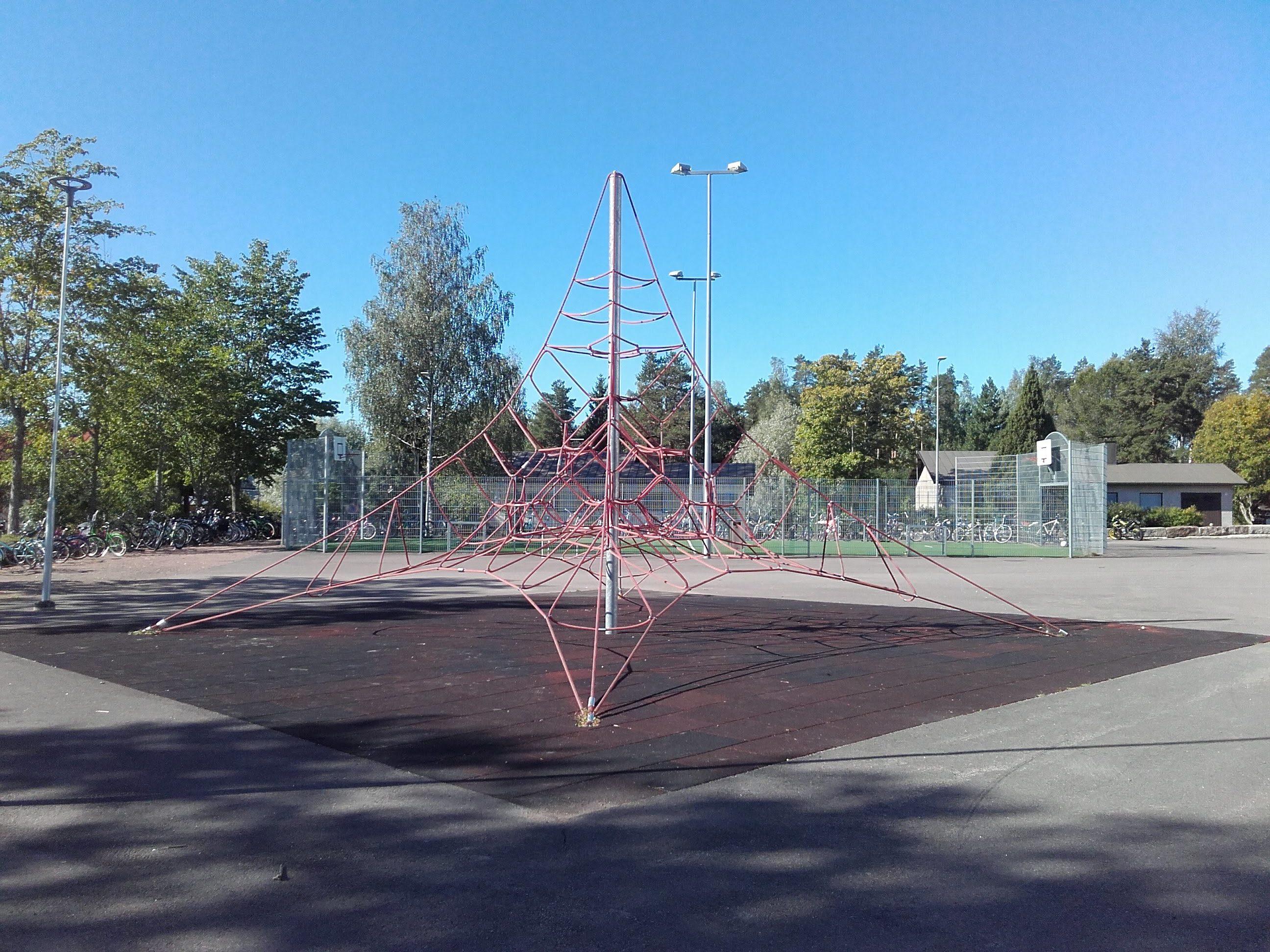Pyramidinmallinen kiipeilyteline koulun pihalla.