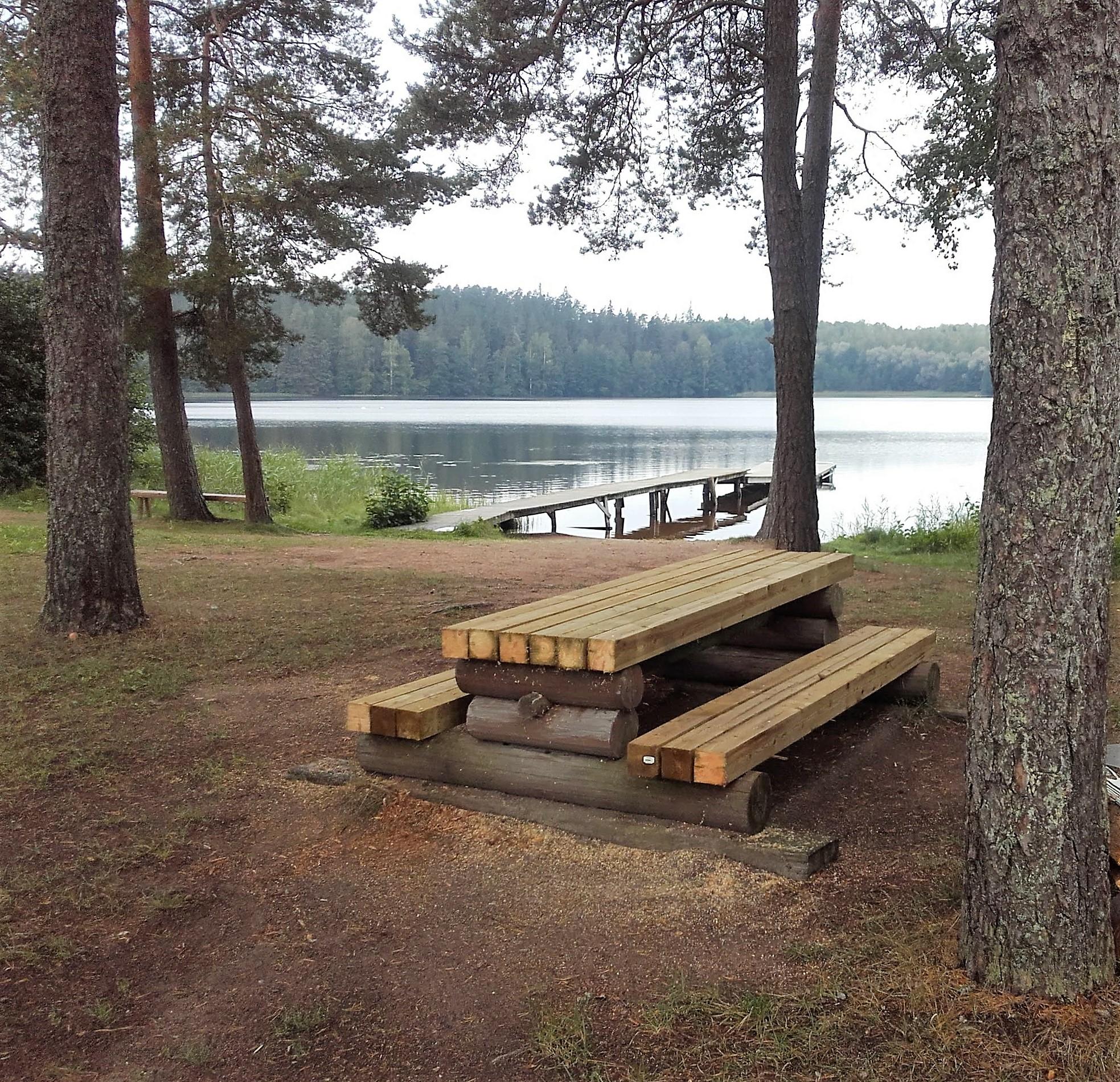 Orijärven uimaranta. Rannalla kiinteä pöytä ja penkit. Vedessä pitkä laituri. Rannalla kasvaa isoja puita.
