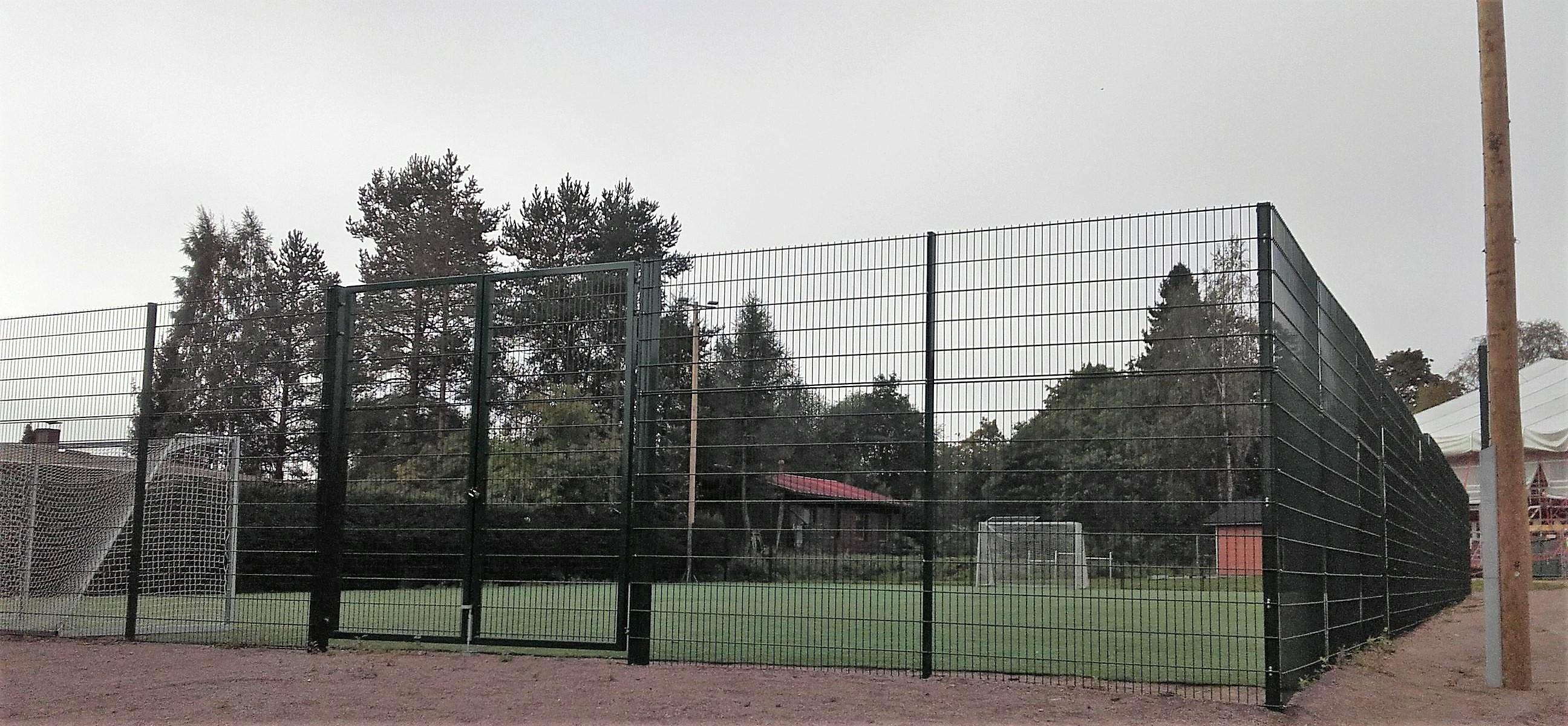 Korkealla metalliverkkoaidalla aidattu tekonurmikenttä. kentällä kaksi jalkapallomaalia.