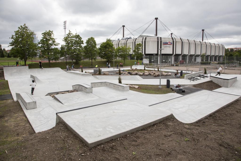 Urheilupuiston skeittiparkki. Betonista muotoiltuja ramppeja. Taustalla Kouvolan jäähalli.