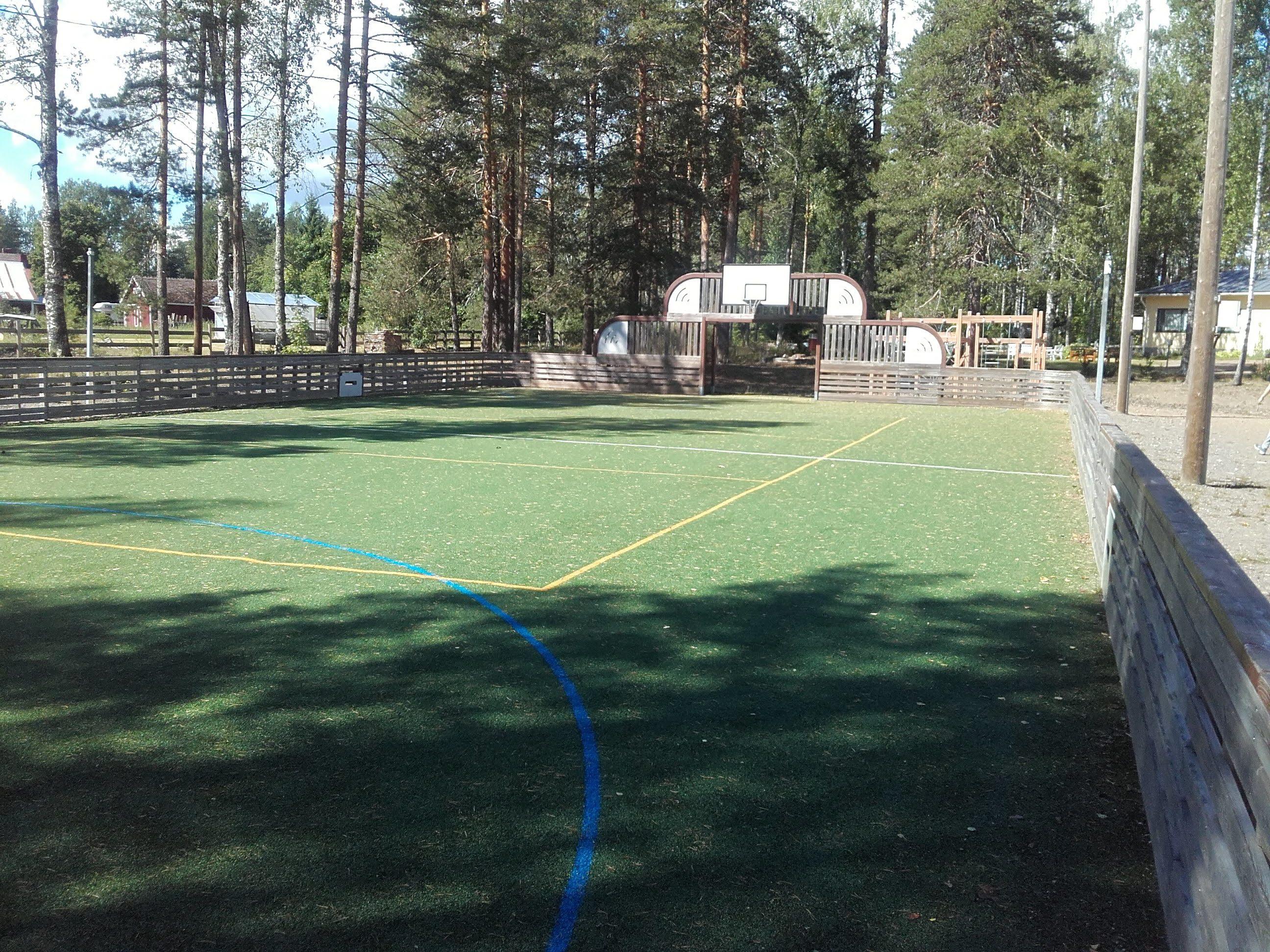 Aidattu tekonurmialue. Puiset laidat. Kentän toisessa päässä koripalloteline sekä jalkapallomaali.