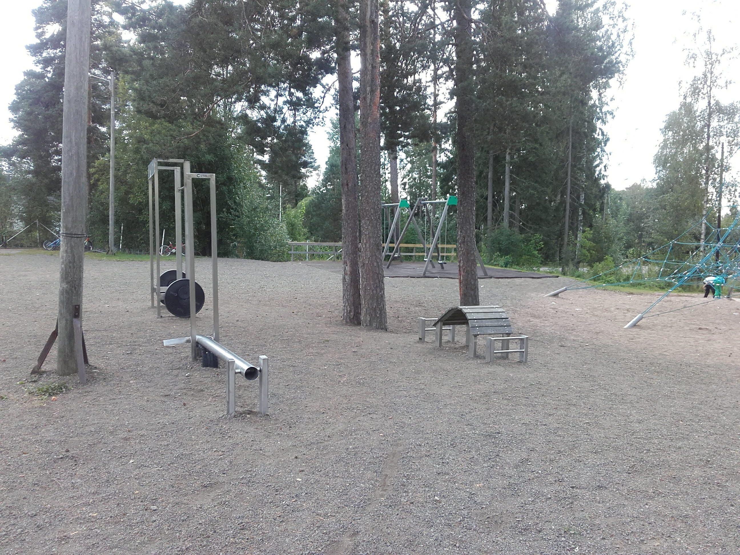 Hiekka-alue jossa muutama puu sekä kolme ulkokuntoilulaitetta.