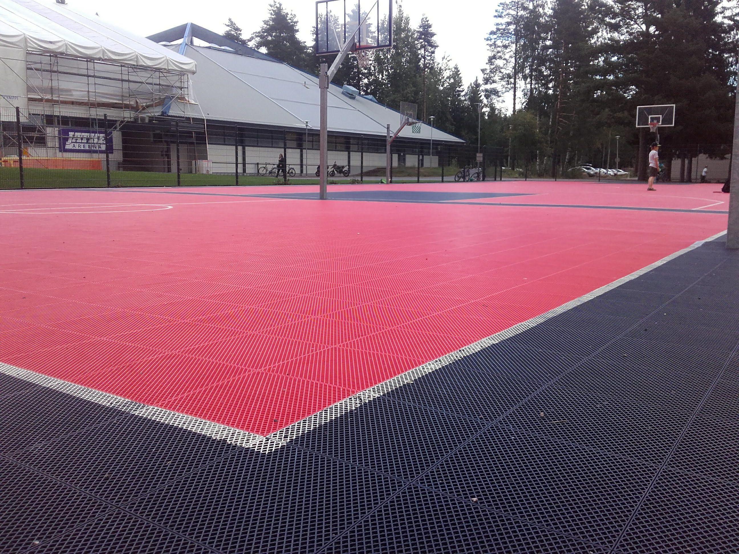 Pelikenttä, keskusta punainen ja reunat mustaa muovimattoa. Kentällä koripallokoreja. Kentän takana Mansikka-ahon liikuntahalli.