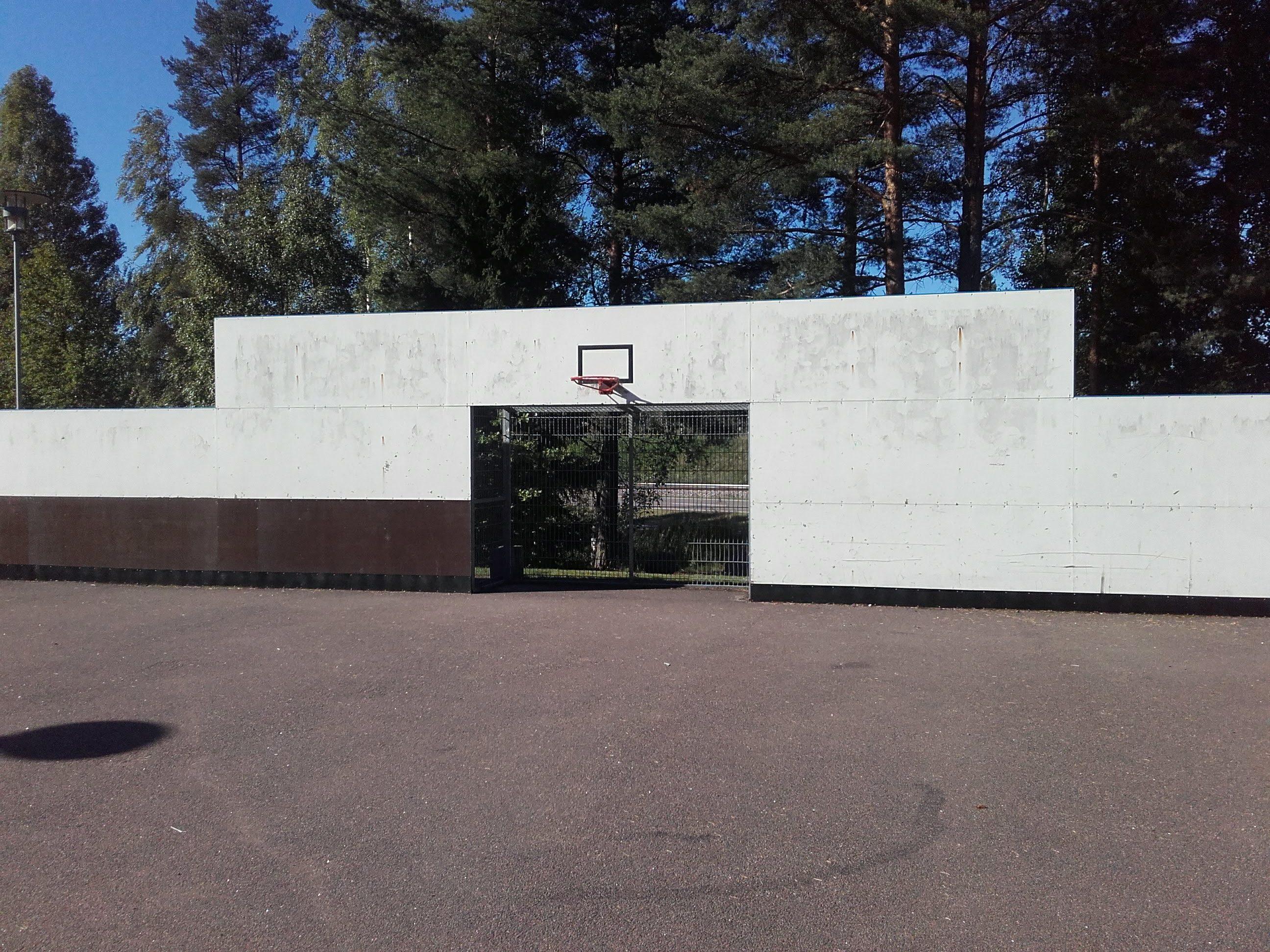 Asfalttikenttä jossa iso valkoinen seinä. Seinässä jalkapallomaali sekä koripalloteline.