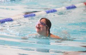 Lapsi ui uimahallissa, uimalassit päässä.