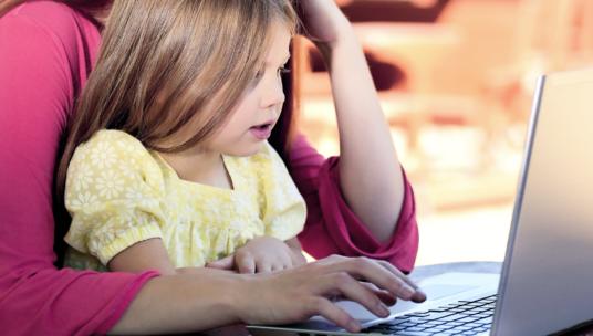 lapsi vanhemman kanssa tietokoneen ääressä