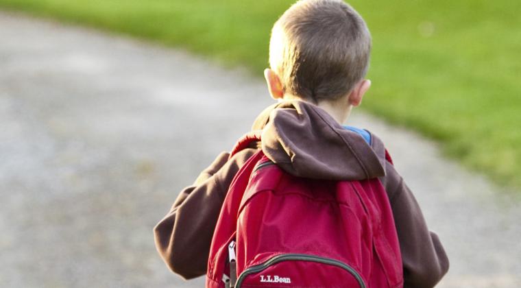 pieni poika, koululainen matkalla kouluun reppu selässä