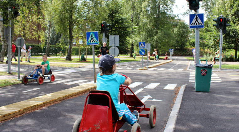 Lapsi ajaa polkuautolla lasten liikennepuistossa pysähtyneenä punaisiin liikennevaloihin.