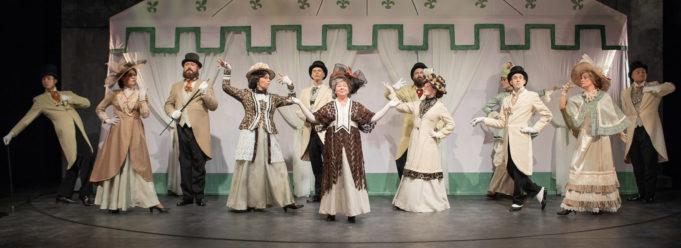 Kouvolan Teatterin näyttelijät lavalla pukeutuneina 1800-luvun lopun henkisiin vaatteisiin.