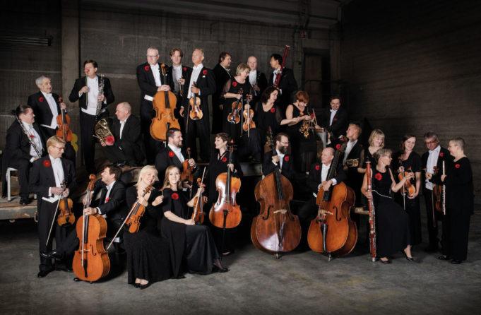 Kymi Sinfonietan kaikki soittajat juhlavaatetuksessa poseeraamassa yhteiskuvassa.
