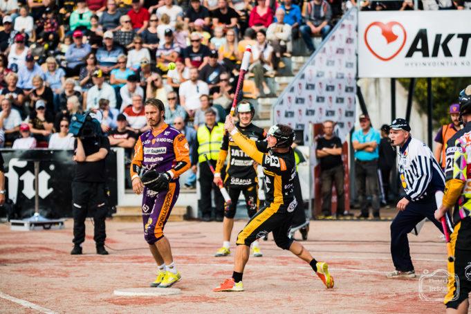 Pesäpalloilija lyömässä palloa suuren yleisön edessä pesäpallo-ottelussa.