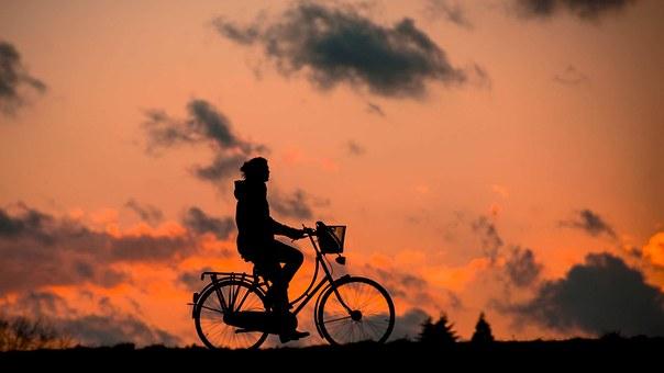Nainen pyöräilee kauniissa iltaruskassa.