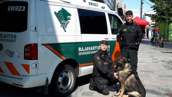 Rajavartiolaitoksen auto, koiranohjaaja ja koira esittelyssä Manskilla.