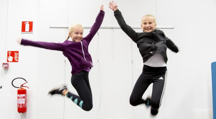 Kaksi tyttöä hyppäävät ilmaan