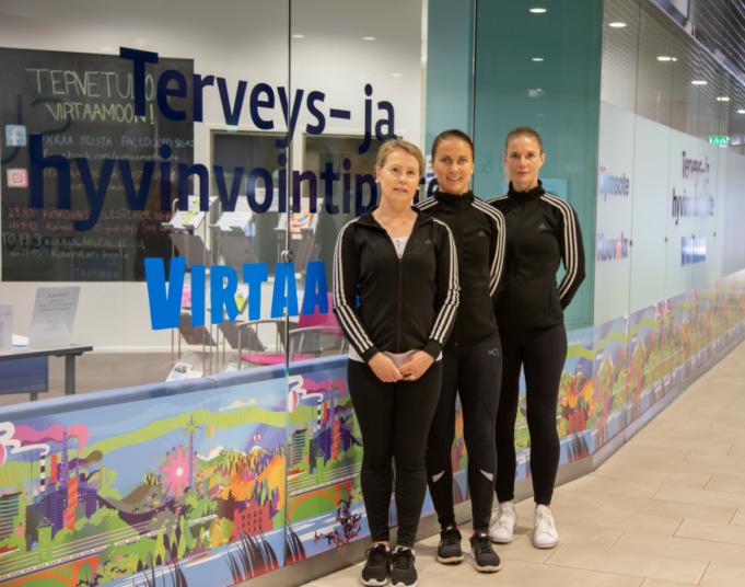 Kolme liikuntaneuvojaa seisoo peräkkäin Terveys- ja hyvinvointipiste Virtaamon edustalla.