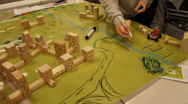Oppilaat rakentamassa ja piirtämässä mielikuvituskaupunkia pelialustalle.