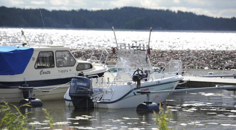 Valkoisia moottoriveneitä Jaalassa järven rannalla..