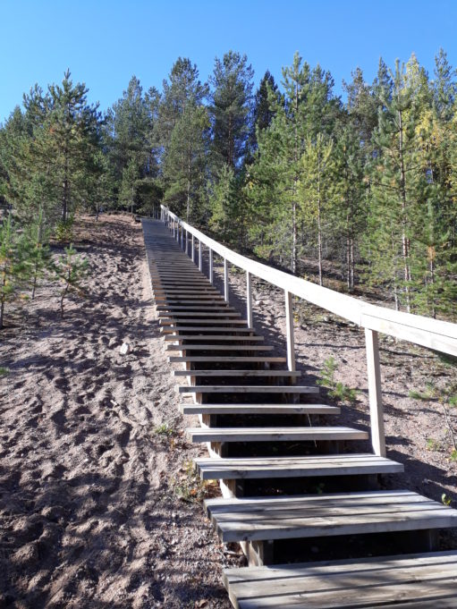 Hiekkaharju jossa puiset portaat. Portaissa kaide ylösmennessä oikealla puolella.
