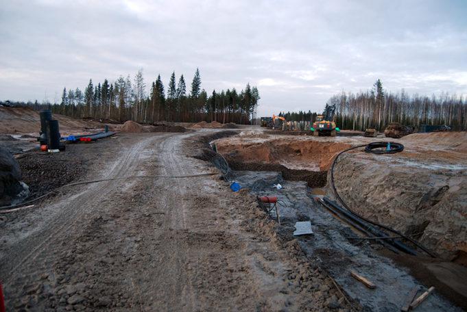 Työmaa-aluetta ja kaivantoja, joihin on vedetty putkia ja kaapeleita. Taustalla kaivinkoneet työssä.