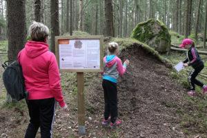 Kuvassa nainen katsoo luontopolun opastaulua ja kaksi tyttöä tutkivat maastoa.