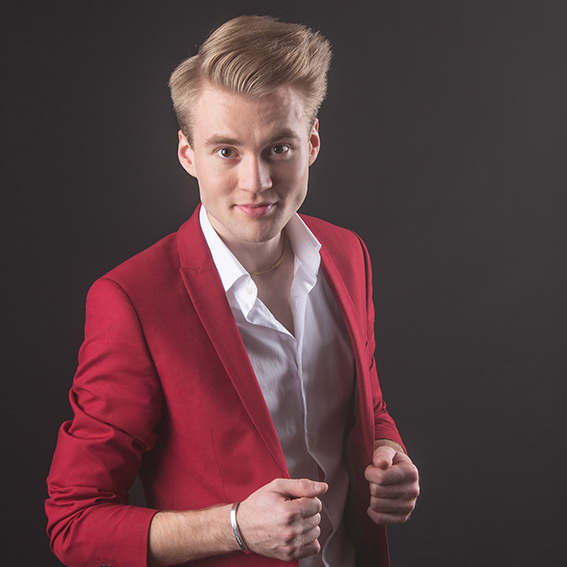 Aatu Itkonen poseeraa punaisessa puvuntakissa kameralle.