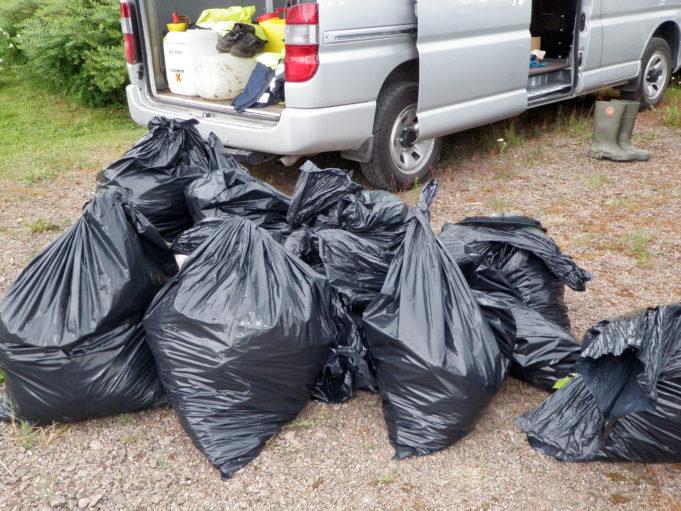Kuvassa täysiä jätesäkkejä maassa harmaan pakettiauton vieressä