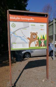 Luontopolun opastalu, jossa teksti Alakylän luontopolku. Taulussa piirroshahmoina karhu ja kettu metsässä.