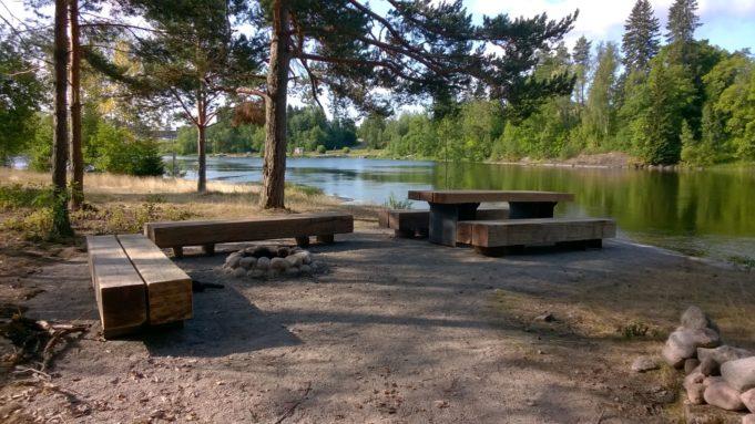 Kuvassa järeät puusta rakennetut penkit ja pöytä joen rannassa. Penkkien edessä kivistä rakennettu nuotiopaikka.