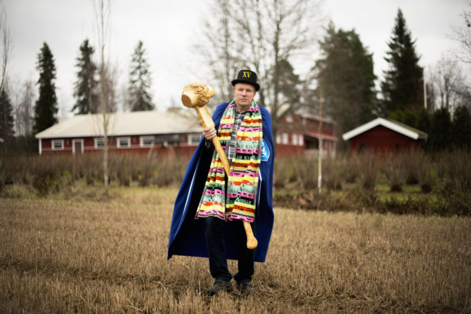 Jukka Naukkarinen seisoo pellolla iso puinen nuija kädessään, viitta harteillaan, silinteri päässään ja värikäs kaulahuivi.