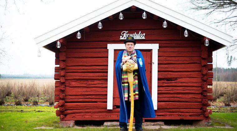 Jukka Naukkarinen punaisen hirsimökin edustalla
