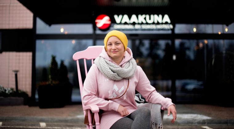 Tiia Valkeapää istuu pinkissä keinutuolissa hotelli Vaakunan edessä