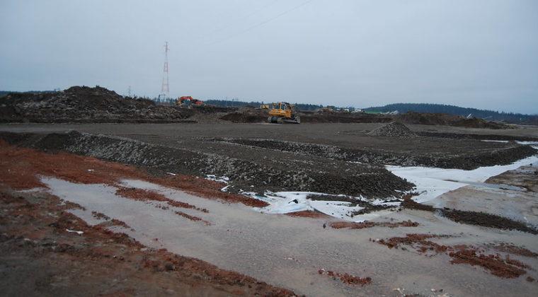 RRT-työmaalla näkyy joulukuussa sorakenttä, jossa on sorakasoja, vesilammikoita ja työkoneita.