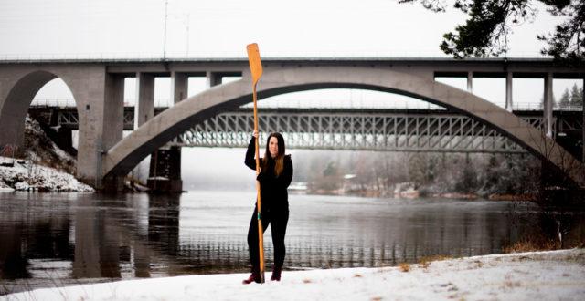 Heini Lämsä seisoo Korian silta taustallaan, kädessä on kirkkoveneen mela.