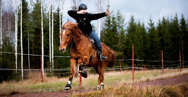 Mies hevosen selässä ja ampuu jousipyssyllä