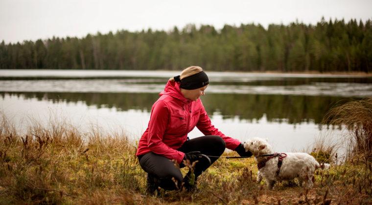 Nainen koiransa kanssa lammen rannalla.