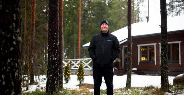 Patrik Lehto seisoo metsässä ja hymyilee.