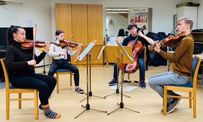 Jousikvartetti soittamassa viuluja musiikkiopiston huoneessa.