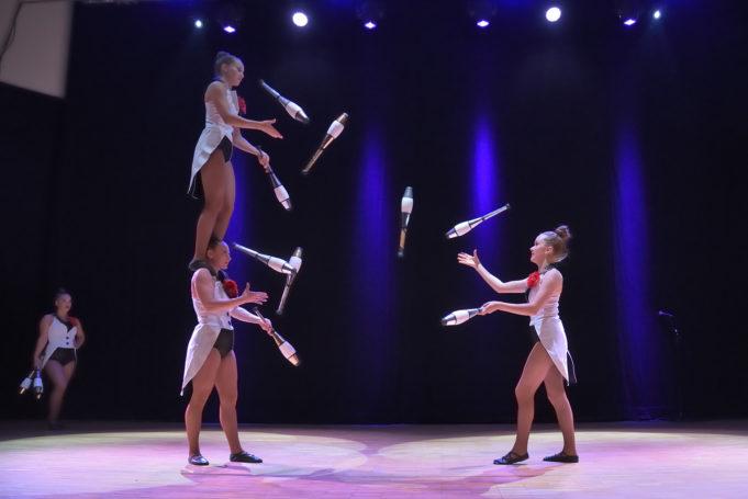 Kolme sirkustaiteilijatyttöä jonglööraa yhdessä keiloilla. Yksi tytöistä seisoo korkealla toisen tytön olkapäilla, mikä lisää tempun vaikeustasoa.